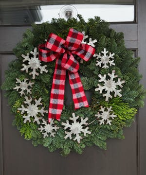 This fragrant wreath is made of mixed evergreens trimmed with pine cones, a festive bow and metal snowflakes. This ships well.