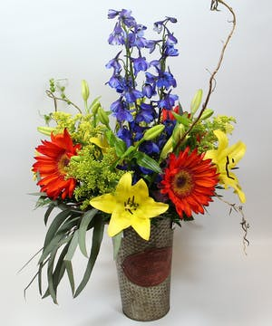 A lavish bouquet of red sunflowers, delphinium, yellow Asiatic lilies and accents in a metal garden tin.