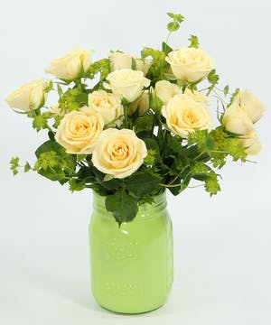 Spray roses with greenery in colored mason jars.