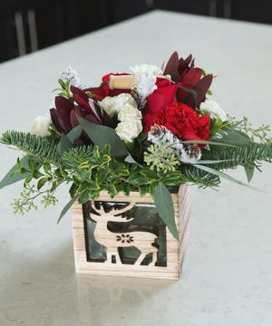 A wooden handled box with cutouts filled with a charming bouquet of red carnations, white pixie carnations, fresh fir, seeded eucalyptus and a snowy pinecone.