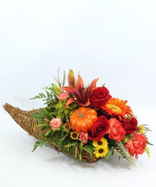 A cornucopia overflows with red sunflowers, orange Asiatic lilies, orange carnations and mini carnations, Viking poms, accents of green wheat, solidago and a pumpkin.