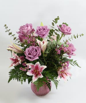 A luxurious bouquet of fragrant Oriental lilies and lavender roses with accents in a glass vase.