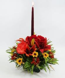 Create a warm holiday table with this seasonal centerpiece.  A 6-inch tapered candle in a hurricane is nestled among  carnations, Asiatic lilies, daisies and Viking poms.
