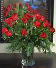 Two dozen premium roses in a glass vase accented with Christmas greens.