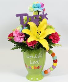 A bright and vibrant mug for the world's best teacher filled with an Asiatic lily, rainbow carnations, kermits and hot pink pixie carnations.