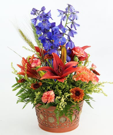 A fall garden look in a basket featuring Asiatic lilies, delphinium, carnations, daisies and seasonal accents.