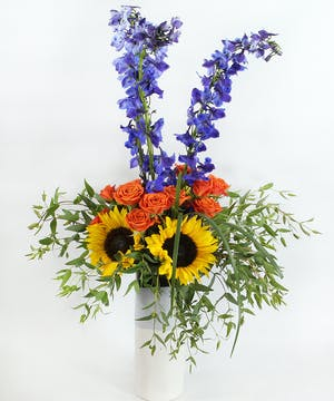Delphinium, sunflowers and orange spray roses with accents in a black, blue and white ceramic vase.