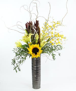 An artisitic design of fragrant Oriental lilies, a sunflower, oncidium orchids, leucadendron, cattails and curly willow in a textured cylinder vase.