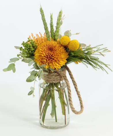 A pair of chrysanthemum buttons, pin cushion protea and craspedia with accents in a small vase with a rope.