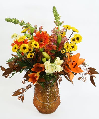 A glass lantern filed with Asiatic lilies, snapdragons, gerbera daisies, fragrant stock, Viking poms and accents. Use the lantern with a candle later.