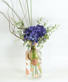 A vase with copper flowers is filled with a stem of hydrangea with accents of steel grass, eucalyptus and curly willow.