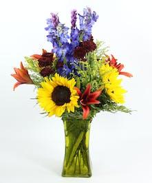 A vibrant design of sunflowers, Asiatic lilies, liatris, delphinium, daisies in a colored glass vase.