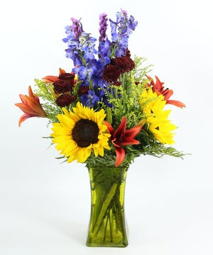 A vibrant design of sunflowers, Asiatic lilies, liatris, delphinium, daisies in a colored glass vase.