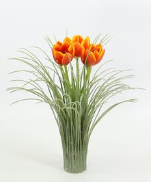Three tulips in a faux grass covered vase.
