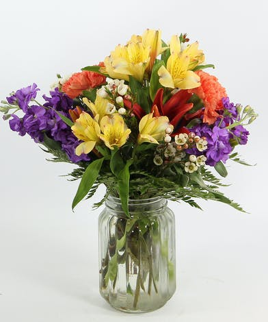 Send this bright bouquet to someone who needs a little sunshine in their day.  Asiatic and Peruvian lilies, fragrant stock and carnations in a clear glass vase.