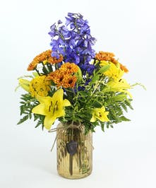 A glass vase with acorns filled with delphinium, Asiatic lilies, Viking poms, yarrow and accents.