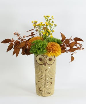 This little owl vase is filled with disbuds, moss carnations, tansy yarrow and tinted eucalyptus.