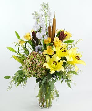 A work of art, The Monet is designed with fragrant Oriental lilies, antique hydrangea, Peruvian lilies, delphinium, cattails and accents in a glass vase.
