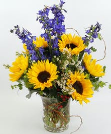 Bright sunflowers, delphinium, and accents of dusty miller, red hypericum and curly willow in a glass vase.