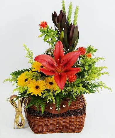 An Asiatic lily, leucadendron, Viking poms safflower and accents are all tucked into a fishing creel. Earn bragging rights with this keeper!