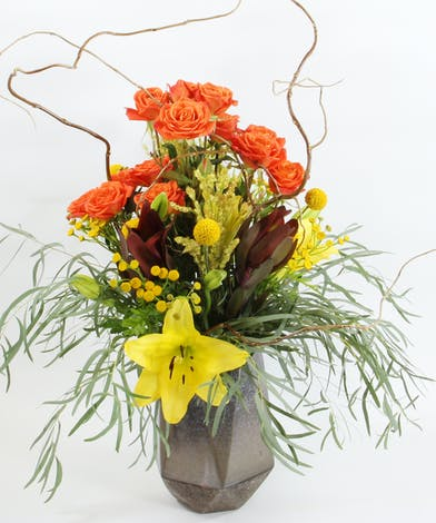 Orange spray roses, Asiatic lilies, tansy yarrow and more fall accents in a hexagon vase.