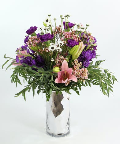 This soft romantic design features pink Asiatic lilies, fragrant purple stock, purple carnations, white mini daisies and accents in a silver vase.