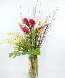 A luxury tropical bouquet of ginger, birds of paradise, oncidium orchids, liatris, bells of Ireland, forsythia and monstera leaves in a tall cylinder vase.