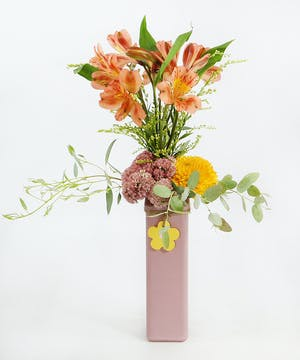 Alstromeria with accents of sedum, chrysanthemum, solidago and gunni eucalyptus in a vase with a flower charm.