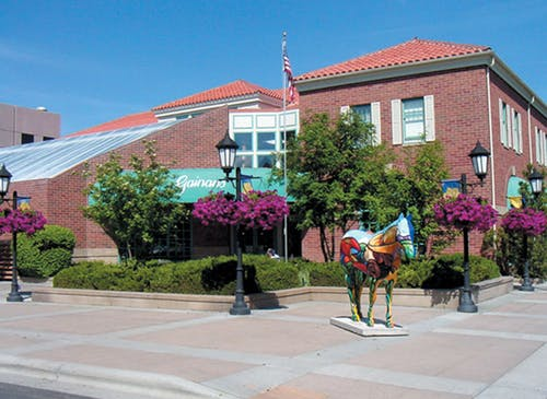 A colorful statue and gorgeous hanging flowers outside our downtown location